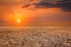 Треснутый ландшафт захода солнца почвы земли Стоковое Изображение
