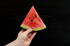 Треугольник арбуза в женской руке на черной предпосылке Стоковое Фото