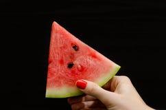 Треугольник арбуза в женской руке на черной предпосылке Стоковая Фотография