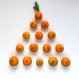 Треугольник tangerines на белой предпосылке Стоковая Фотография