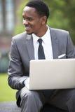 Трехчетвертной портрет Афро-американского бизнесмена работая на компьтер-книжке outdoors Стоковые Фото