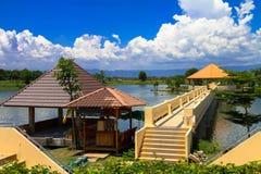 Триангулярная крыша имеет длинный коридор к середине воды, с зелеными горами, белыми облаками и голубыми небесами стоковые фото