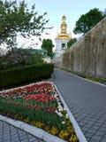 Триангулярный flowerbed с пестроткаными тюльпанами против красивой церков церков в расстоянии Стоковое Фото