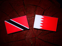 Тринидад и Тобаго сигнализируют с бахрейнским флагом на isol пня дерева Стоковая Фотография