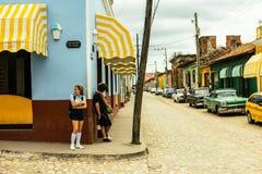 Тринидад, Куба - 2019 Кубинськая девушка со школьной формой на угле улицы ждать местный автобус стоковые изображения