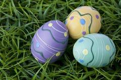 Трио красочных пасхальных яя кладя в яркую ую-зелен траву Стоковые Фото