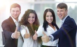 Триумфальная команда дела держа большие пальцы руки вверх Стоковая Фотография