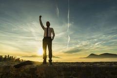 Триумфальный бизнесмен в белой рубашке стоя outdoors с его стоковое изображение