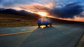 Трицикл солнечного света облака дороги захода солнца стоковое изображение