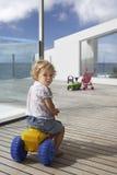 Трицикл игрушки катания мальчика на деревянном крылечке Стоковые Изображения