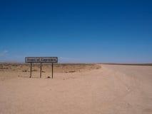 Тропик линии signage козерога вдоль дороги пустыни с синью Стоковая Фотография
