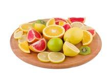 Тропические плодоовощи лежат на деревянной круглой доске на предпосылке изолированной белизной взгляд со стороны под углом Стоковая Фотография RF