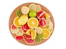 Тропические плодоовощи лежат на круглой деревянной доске на предпосылке изолированной белизной Стоковые Изображения RF