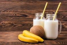 Тропические плодоовощи и бутылки молока на коричневой предпосылке Опарникы каменщика вполне молока с соломами Экзотический кокос  Стоковые Фото
