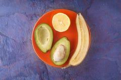 Тропические плодоовощи на оранжевой плите на голубой предпосылке Стоковое Изображение