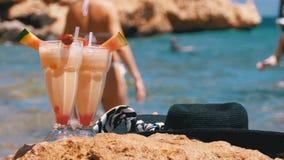 Тропические свежие сок, шляпа и стекла на пляже Египта стоят на утесе Красным Морем видеоматериал