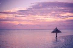 Тропический заход солнца пляжа с парасолем в острове Мальдивов стоковые фото
