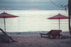 Тропический заход солнца пляжа с сценарным взглядом от sunbed с зонтиком Стоковые Фото