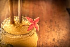 Тропический коктейль в стеклянном опарнике с цветком и соломой льда в винтажных живых оранжевых желтых цветах на стиле деревянног стоковые изображения