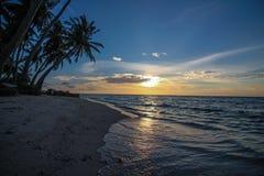 Тропический пляж на заходе солнца Стоковая Фотография