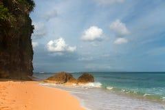 Тропический пляж с желтым песком, лазурным океаном и большим утесом Стоковое фото RF