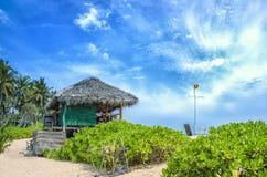 Тропический пляж с коттеджем стоковое изображение