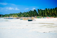 Тропический пляж с белым песком с зелеными пальмами и припаркованными рыбацкими лодками в песке Экзотический рай острова Стоковая Фотография RF