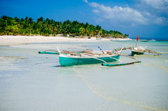 Тропический пляж с белым песком с зелеными пальмами и припаркованными рыбацкими лодками в песке Экзотический рай острова Стоковая Фотография