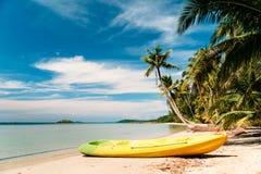 Тропический пляж с изогнутыми пальмами и желтым каное Стоковые Фото