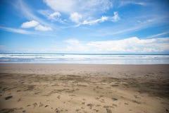 Тропический экзотический пляж с вулканическим песком, голубым небом с облаками никто стоковое фото