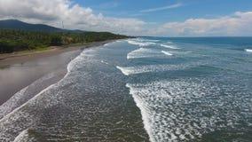 Тропический экзотический пляж с вулканическим песком, голубым небом с облаками никто стоковая фотография