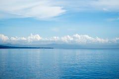 Тропический seascape с дистантным островом и голубым небом Расслабляющий вид на море с неподвижной морской водой Стоковые Изображения RF