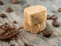 Тростниковый сахар Брайна с кофейными зернами на деревенской деревянной предпосылке Стоковые Фото