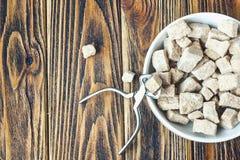 Тросточка и схваты желтого сахарного песка на деревянной предпосылке Стоковые Изображения RF