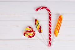 Тросточка конфеты и красочные яркие леденцы на палочке на деревянной доске Стоковая Фотография