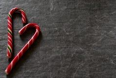 Тросточка конфеты на черной мраморной предпосылке Стоковые Изображения RF