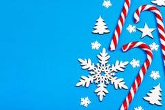 Тросточка конфеты рождества лежала равномерно в строке на голубой предпосылке с декоративными снежинкой и звездой Плоские положен Стоковое фото RF