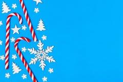 Тросточка конфеты рождества лежала равномерно в строке на голубой предпосылке с декоративными снежинкой и звездой Плоские положен Стоковая Фотография