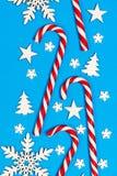 Тросточка конфеты рождества лежала равномерно в строке на голубой предпосылке с декоративными снежинкой и звездой Плоские положен Стоковые Фото