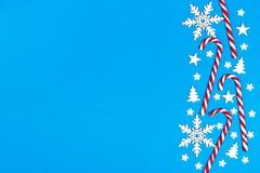 Тросточка конфеты рождества лежала равномерно в строке на голубой предпосылке с декоративными снежинкой и звездой Плоские положен Стоковое Изображение RF