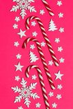 Тросточка конфеты рождества лежала равномерно в строке на розовой предпосылке с декоративными снежинкой и звездой Плоские положен Стоковая Фотография