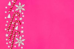 Тросточка конфеты рождества лежала равномерно в строке на розовой предпосылке с декоративными снежинкой и звездой Плоские положен Стоковые Изображения RF