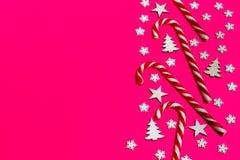 Тросточка конфеты рождества лежала равномерно в строке на розовой предпосылке с декоративными снежинкой и звездой Плоские положен Стоковое Фото