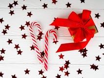Тросточка конфеты рождества на белой деревянной предпосылке, подарочных коробках красного цвета оформлений рождества Стоковые Фото