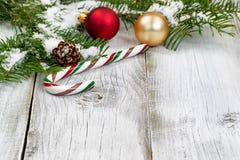 Тросточка конфеты с снегом покрыла ветви и орнаменты ели Стоковые Изображения