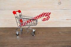 Тросточка конфеты Xmas в вагонетке покупок, рождестве или продаже зимы стоковая фотография