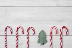 Тросточки и рождественская елка конфеты рождества на белой деревянной предпосылке стоковые фотографии rf