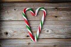 2 тросточки конфеты помещенной в сердце формируют на деревянной предпосылке Стоковые Изображения RF