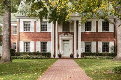 Тротуар водит к высококачественному дому с белыми шторками и столбцами и кресло-качалкам на крылечке через высокие деревья и sca  стоковая фотография