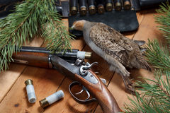 Трофей звероловства - куропатка, винтовка, патронная лента, боеприпасы, на деревянных досках Стоковая Фотография RF